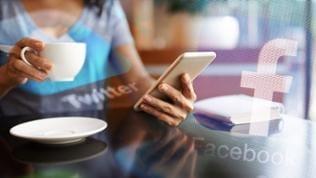 Eine Frau sitzt morgens mit ihrem Smartphone am Frühstückstisch.