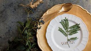 Ein goldener Platzteller mit weißem Porzellanteller. Daneben goldene Löffel, eine Serviette und ein kleiner goldener Deko-Hirsch.