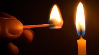 Kerze wird mit Streichholz angezündet