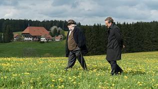 Hermann und Bernhard gehen über eine Frühlingswiese, im Hintergrund der Fallerhof