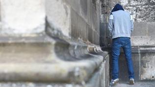 Ein Mann steht an einer Wand und pinkelt dagegen, von hinten fotografiert