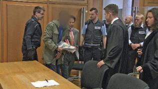 Mehrere Polizisten, zwei Anwälte in einem Gerichtssaal, Angeklagter verfremdet
