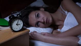 Frau liegt im Bett und schaut auf ihren Wecker der vier nach drei Uhr nachts zeigt.