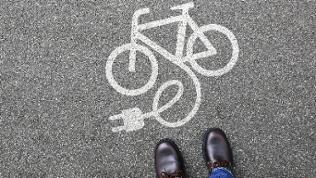 Ein Mann steht auf einem Gehweg. Auf dem Gehweg sieht man die Zeichnung eines eBikes.