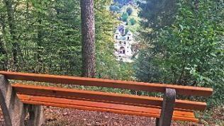 Über eine Sitzbank im Wald hinweg fällt der Blick auf ein großes Gebäude mit Türmen im Tal