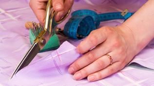 Stoff wird mit Schere geschnitten