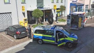 Polizisten mit Einsatzfahrzeugen vor einem Gebäude
