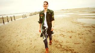 Vincent Gross läuft an einem Strand entlang und schaut lachend in die Kamera.
