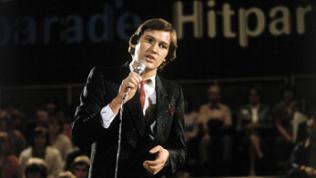 Der Sänger Johnny Logan performt ein Lied auf einer Bühne.