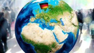 Deutschland Fahne steckt in einer Weltkugel, im Hintergrund laufen Menschen