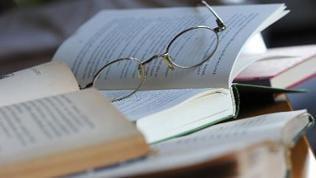 Eine Lesebrille liegt auf einem Stapel aufgeklappter Bücher