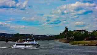 Ein Ausflugsschiff ist auf der Mosel kurz vor der Mündung in den Rhein am Deutschen Eck in Koblenz unterwegs