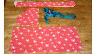 Schnittteile mit Stecknadeln auf den Stoff stecken. Rechteck, Tasche und Bindeband je 1 mal zuschneiden.