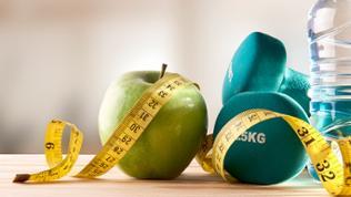Ein Apfel neben zwei Gewichten und einer Wasserflasche, davor ein Maßband.