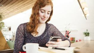 Eine junge Frau sitz an einem Tisch mit einer Tasse Kaffee und hält ein Smartphone in der Hand.