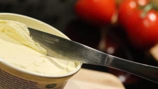 Messer steckt in einem Becher voller Margarine