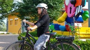 Mädchen mit Helm auf einem E-Bike