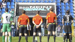 Schiedsrichter und Spieler stehen nach dem Einlaufen vor einem Plakat gegen Gewalt.