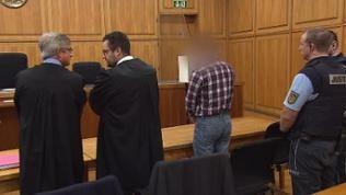 Angeklagter, zwei Anwälte und zwei Polizisten stehen vor Urteilsverkündigung im Amtsgericht Heilbronn und warten auf Eintreffen des Richters
