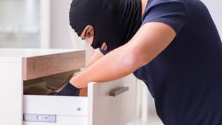 Ein maskierter Einbrecher wühlt in einer Schublade.