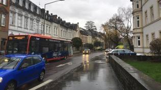 Eine vom Regen nasse Straße mit Autos und einem roten Bus.