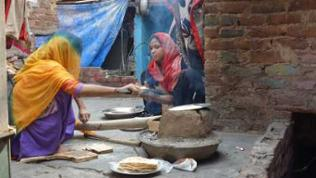Frauen in den Slums von Delhi (Indien) backen Fladenbrot