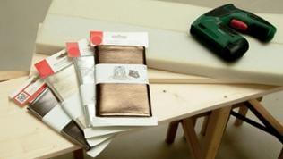 Das schmalere Brett wird auf den Schaumstoff gelegt und beides in den Stoff eingeschlagen.