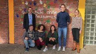 """Frank Schuhmacher, Schulleiter des Hohenlohe Gymnasiums in Öhringen mit Lehrern und Schüler vor einer Wand mit Aufschrift """"Schule ohne Rassismus"""""""