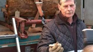 Ein Mann hält den Zünder einer entschärften Bombe in der Hand, im Hintergrund der verrostete Blindgänger