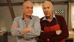 Heinz und Franz stehen beide mit verschränkten Armen nebeneinander