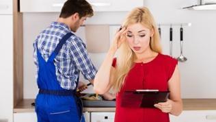 Eine blonde Frau im roten Kleid schaut entgeistert auf ein Klemmbrett, im Hintergrund ist ein Handwerker am arbeiten