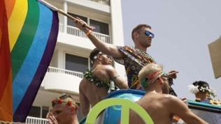 Männer in Kostümen mit Regenbogenfahne bei einer Parade