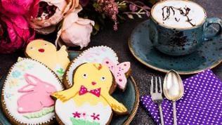 Auf einem Tisch befinden sich eine Tasse und ein Teller, auf dem Teller liegt Ostergebäck mit Verzierungen aus Zucker: Küken, Hase, Ei.