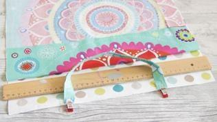 Die beiden Stoffteile für die Tasche rechts auf rechts zusammenlegen und die Henkel jeweils 10 cm von den Außenkanten zwischen den Stofflagen feststecken.