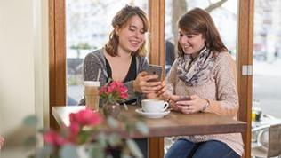 Das Bild zeigt zwei Frauen, die auf ihr Smartphone schauen