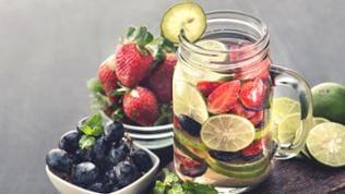 Eine Glas Wasser mit Limetten, Erdbeeren und Heidelbeeren.