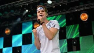 Der Sänger Vincent Gross steht mit Stirnband auf der Bühne