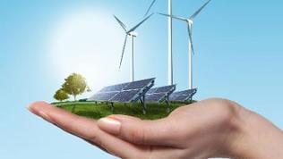 In einer Frauenhand befindet sich eine Wiese mit einer Photovoltaikanlage und Windrädern, im Hintergrund ist ein blauer Himmel zu sehen.