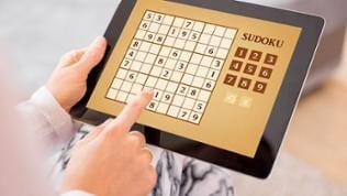Eine Frau spielt auf einem Tablet Sudoku