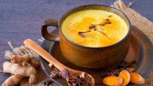 Eine braune Tasse gefüllt mit goldener Milch neben Kurkuma und Arnis und einem Löffel.