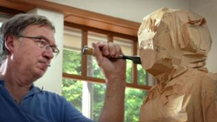 Bildhauer Stephan Balkenhol setzt das Stemmeisen am Kopf einer Holzfigur an