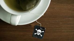 In einer Teetasse liegt ein Teebeutel mit einem Totenkopf aufgedruckt.