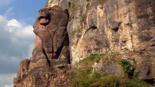 Monumentale Löwenskulptur aus Sandstein vor einem Felsen