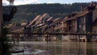 Häuserzeile nah am Fluss mit Brücke