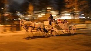 Wiener Fiaker mit Fahrgästen in der Nacht bei schneller Fahrt