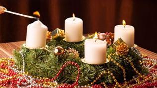 vierte Kerze am Adventskranz wird angezündet