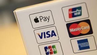 Ein Apple Pay Service Logo wird zusammen mit anderen wichtigen Logos für Zahlungsdienste an einer Kasse in einem Apple Store angezeigt.