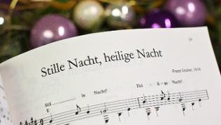 Noten zum Weihnachtslied «Stille Nacht, heilige Nacht», im Hintergrund Christbaumkugeln