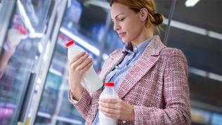 Eine Frau liest in einem Supermarkt die Inhaltsstoffe auf einer Milchflasche.