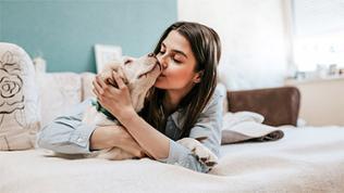 Eine Frau liegt mit ihrem Hund auf dem Bett und küsst ihn.